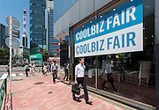 Salarymen or male office workers walk past a clothes store advertising a cool biz campaign. Shimbashi, Tokyo, Japan. Friday June 3rd 2016 Cool biz was a campaign started by the Japanese Ministry f the Environment in 2005 suggesting that Japense workers dressed more casually in the summer heat and thus use air-conditioning less in an effort to reduce electricity usage.