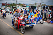 24 OCTOBER 2012 - PATTANI, PATTANI, THAILAND:  A Muslim family rides through a market in Pattani, Thailand.  More than 5,000 people have been killed and over 9,000 hurt in more than 11,000 incidents, or about 3.5 a day, in Thailand's three southernmost provinces and four districts of Songkhla since the insurgent violence erupted in January 2004, according to Deep South Watch, an independent research organization that monitors violence in Thailand's deep south region that borders Malaysia. Muslim extremists are battling the Thai government and its symbols, like schools and Buddhist facilities.    PHOTO BY JACK KURTZ