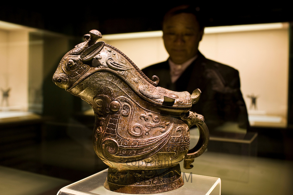Man looks at Fu Yi Gong wine vessel on display in glass case at the Shanghai Museum, China