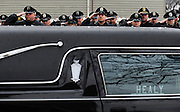 Jonathan Miano/Staff Photographer/Naperville Sun.20100222 Monday, Aurora..Area police officers salute as the casket of retired Sergeant John M. Burghardt, a 23 year veteran of the Naperville Police Department, is carried out of his funeral at St. Joseph Catholic Church in Aurora Monday. Burghardt died of natural causes...