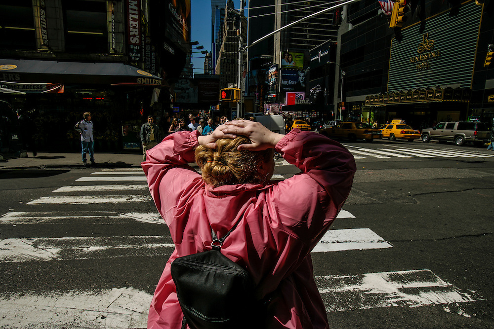 A woman waits on a crosswalk in New York.