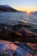 Two girls play at Telegrafbukta at the south end of Tromsoya island on January 21st watching return of the sun after its two-month absence; Tromso, Norway.