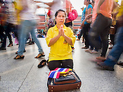 05 DECEMBER 2014 - BANGKOK, THAILAND: People walk past a woman praying for the health of Bhumibol Adulyadej, the King of Thailand, in the Grand Palace Friday morning. Thais marked the 87th birthday of the King Friday. The revered Monarch was scheduled to make a rare public appearance in the Grand Palace but cancelled at the last minute on the instructions of his doctors. He has been hospitalized in Siriraj Hospital, across the Chao Phraya River from the Palace, since early October.    PHOTO BY JACK KURTZ