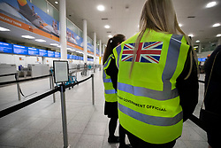 © Licensed to London News Pictures. 23/09/2019. Gatwick, UK. British Government officials wearing hi-vis vests work near closed Thomas Cook check-in desks at Gatwick Airport after the travel firm collapsed overnight. The 178 year old travel operator has gone in to liquidation after rescue talks failed overnight. This will trigger the largest peacetime repatriation as more than 150,000 British holidaymakers will need to be brought home. Photo credit: Peter Macdiarmid/LNP