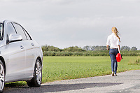 Full length rear view of woman carrying gas can leaving behind broken down car at countryside