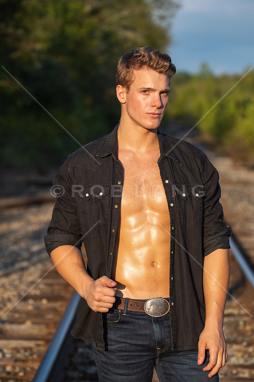 sexy muscular man with open shirt on a railroad track