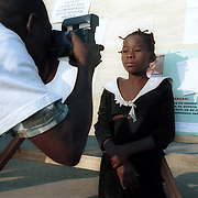 September 13, 2002                   Luanda, Angola<br /> <br /> Maria Dominga, 9,  has her photo taken by an Angolan social worker at a public square in Luanda, Angola, which is informally called the Meeting Place. Dominga has been seperated from her family and hopes that she will be reunited with them through the help of one of the social organizations assisting people at the Meeting Place. <br /> Photo by Lori Waselchuk/South Photographs