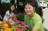 Grandmother and granddaughter loading flowers into back of SUV portrait