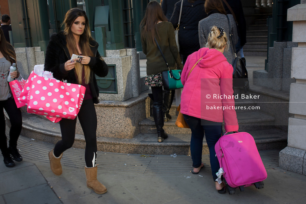 Women with matching coloured pink possessions in a City of London street.