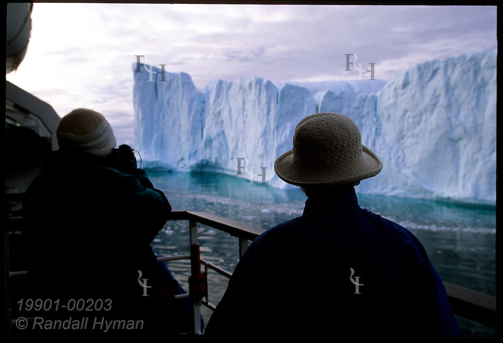 Passengers aboard the Clipper Adventurer cruise ship stand along upper deck to admire towering Disko Bay iceberg; Ilulissat, Greenland