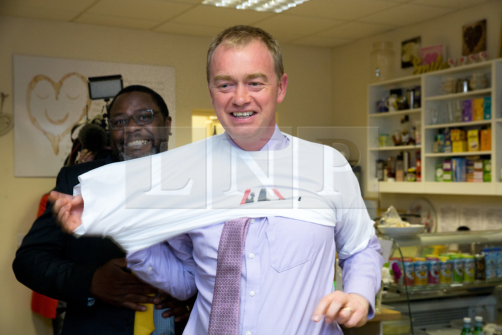 © Licensed to London News Pictures. 15/05/2017. Olton, Solihull, UK. Liberal Democrats Leader Tim Farron in Solihull to support Ade Adeyeno the local LibDem candidate (wearing spectacles). Tim Farron putting on a Fair funding for all schools T Shirt. Photo credit: Dave Warren/LNP
