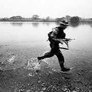 A Government soldier splashes across a river in pursuit of escaping FARC rebels after a firefight. The FARC had been holding 40 civillians hostage at an illegal roadblock to entice the counter inurgency force to engage them.<br />