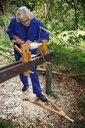 Volunteer at Bestwood Country Park, Nottinghamshire, part of Sherwood Forest, using pole lathe to turn green ie unseasoned wood: this craft was known as bodging.