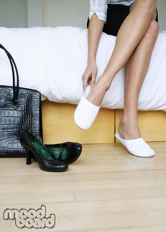 Young woman sitting on bed putting on slippers bag and shoes on floor low section