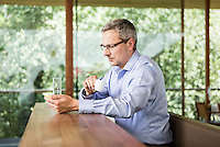 Österreich, Geschäftsmann mit Smartphone bei Kaffeepause an Theke in Restaurant, Casual Look