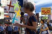 An older Japanese woman speaks at a  small protest against the staging of the Olympic Games in Shinjuku, Tokyo, Japan Friday June 30th 2017. Though mostly popular with the Japanese population he staging of the 2020 Olympic Games in Tokyo is felt by some to be a waste of money when the economy is bad, causing increasing poverty rates and with problems in the Tsunami damaged North East coast still not fully resolved.