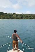 deckhand Patrick Atu holds gaff to pick up mooring line while approaching Ika Lahi International Fishing Lodge aboard Reel Addiction, Hunga Island, Vava'u, Kingdom of Tonga, South Pacific