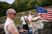 Phil Grundleson, left, and Jesse Schilligo toss the carp off their boat after the first heat at the 10th Annual Redneck Fishin' Tournament held Saturday, Sept. 5, 2015, in Bath, ILL. The only fishing tournament where poles are not allowed and you must catch the Asian Carp with a net or your hands as they fly through the air. This year 5,839 if the invasive species were removed from the Illinois River during the tournament. Photography by Rob Hart