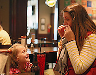 Lucy Giorgio (from left), 4, laughs as her mother, Katie Giorgio of Cedar Rapids puts up an adhesive mustache at a Movember get together during the Iowa football game at Dublin City Pub in Cedar Rapids on Saturday, November 17, 2012.