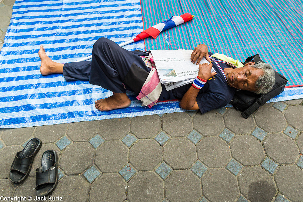 26 NOVEMBER 2013 - BANGKOK, THAILAND: An anti-government protestors sleeps in the courtyard at the Ministry of Finance in Bangkok. Protestors opposed to the government of Thai Prime Minister Yingluck Shinawatra spread out through Bangkok this week. Protestors have taken over the Ministry of Finance, Ministry of Sports and Tourism, Ministry of the Interior and other smaller ministries. The protestors are demanding the Prime Minister resign, the Prime Minister said she will not step down. This is the worst political turmoil in Thailand since 2010 when 90 civilians were killed in an army crackdown against Red Shirt protestors. The Pheu Thai party, supported by the Red Shirts, won the 2011 election and now govern. The protestors demanding the Prime Minister step down are related to the Yellow Shirt protestors that closed airports in Thailand in 2008.     PHOTO BY JACK KURTZ