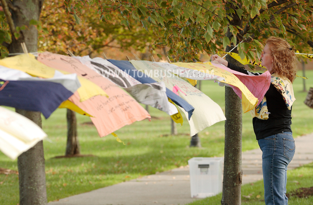 Goshen, NY -  A woman hangs shirts on a line as part of the Clothesline Project, a display of shirts designed by women survivors of violence, in front of the Orange County Government Center in Goshen on Oct. 2, 2008. The shirts are color coded to show the form of abuse and whether the victim survived the abuse they experienced.