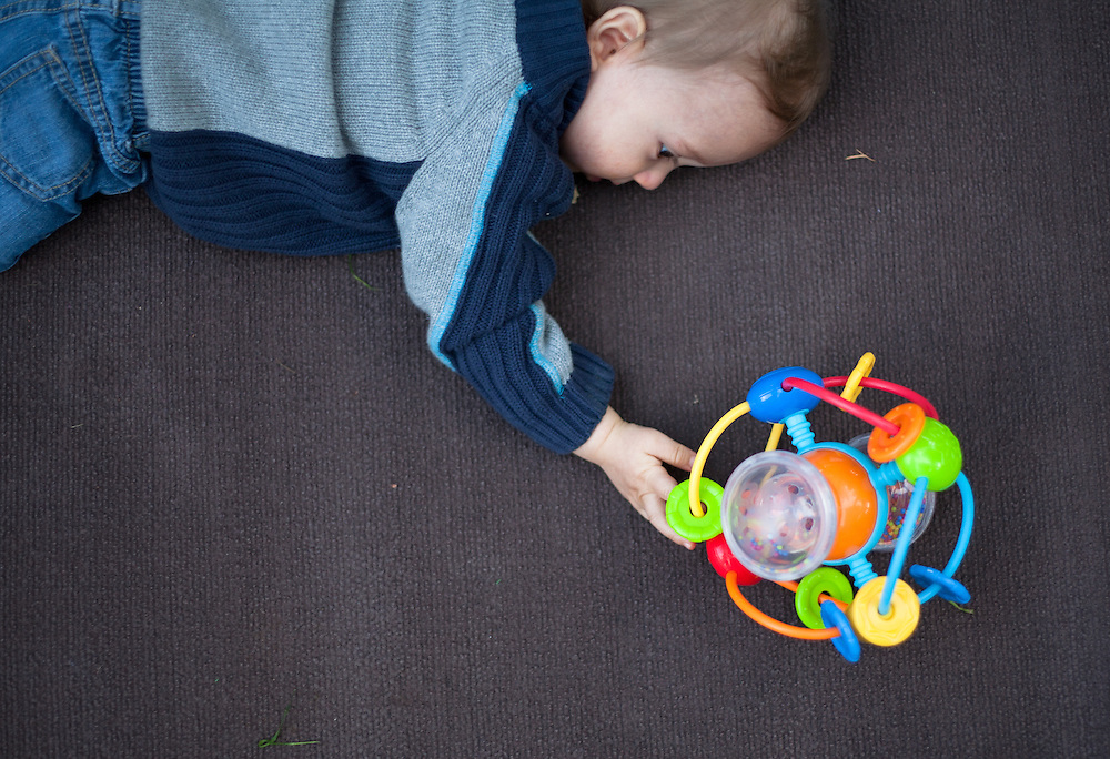 Portraits of a baby boy playing by himself outside on a blanket in a grassy area with a toy
