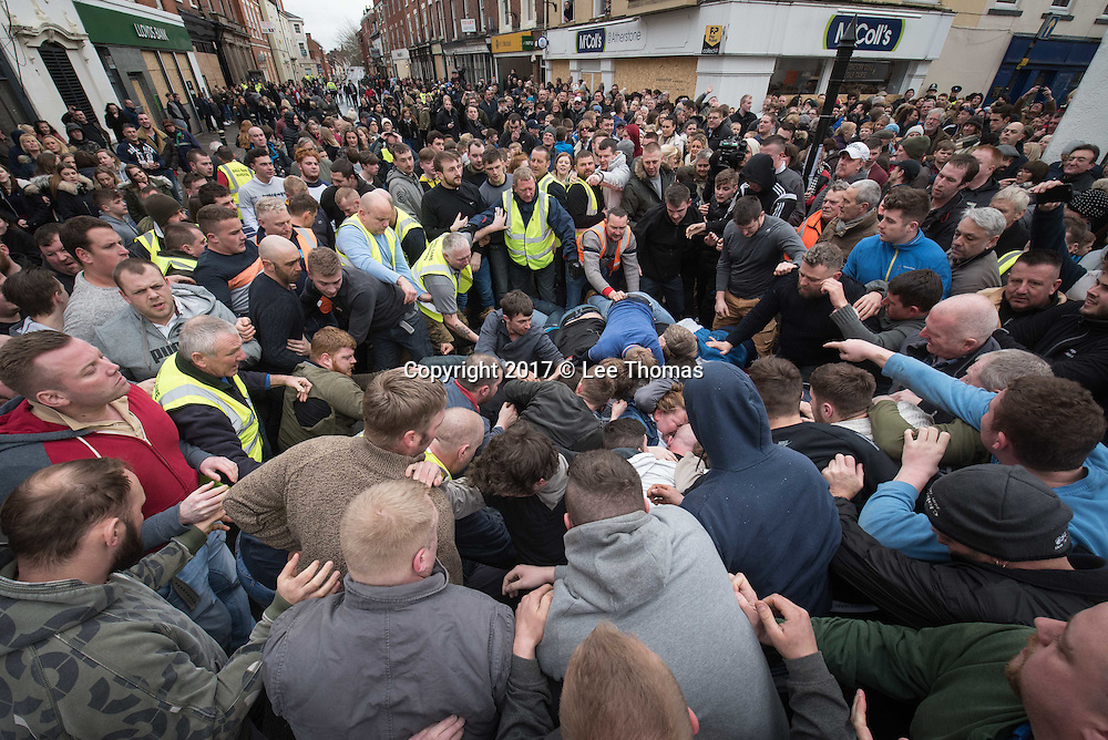 "Atherstone, Warwickshire, UK. 28th February 2017. Pictured:  The ball is released to the crowds. / Hundreds of people of all ages flood into the Warwickshire town of Atherstone to either participate or watch the infamous Atherstone Ball Game. The event is being held for the 818th time opening when this year's celebrity, Eastenders star Annette Badland, throws the ball into the crowd of people. The Atherstone Ball Game is an ancient Shrove Tuesday tradition in which the people of this rural North Warwickshire town awaken and literally brawl over a large ball up and down the town's small ancient streets. Shops are boarded up, local schools are closed and towns people of Atherstone gather in the main street at 3pm with only one rule in mind, the ball cannot be taken outside the town. Anything and everything else goes. The winner in this no holds barred contest is the person holding onto the ball at 5pm. This traditional Shrove Tuesday Ball Game has been held annually since the early 12th Century and is one of Atherstone's claims to fame. The origin of the game, in the reign of King John, is thought to have been a ""Match of Gold that was played between the Warwickshire Lads and the Leicestershire Lads on Shrove Tuesday"".  // Lee Thomas, Tel. 07784142973. Email: leepthomas@gmail.com  www.leept.co.uk (0000635435)"