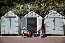 © Licensed to London News Pictures. 26/06/2018. Bournemouth, UK. Sun seekers relax in front of their beach hut in hot afternoon sunshine at Bournemouth. Most of the UK is enjoying summer temperatures in the high 20's today. Photo credit: Peter Macdiarmid/LNP