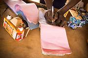 A man fills an invoice after making a sale at the Village Artisanal de Ouagadougou, a cooperative that employs dozens of artisans who work in different mediums, in Ouagadougou, Burkina Faso, on Monday November 3, 2008.