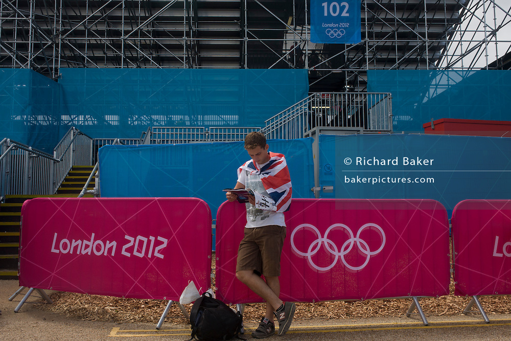 Alongside the Olympic rings logo, a young Brit reads from his official programme before the start of the canoe slalom heats at the Lee Valley White Water Centre, north east London, on day 3 of the London 2012 Olympic Games.