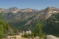 Group of young adults sitting on cliff gazing at view of Silver Star Mountain near the Pacific Crest Trail and Cutthroat Pass. North Cascades Washington.