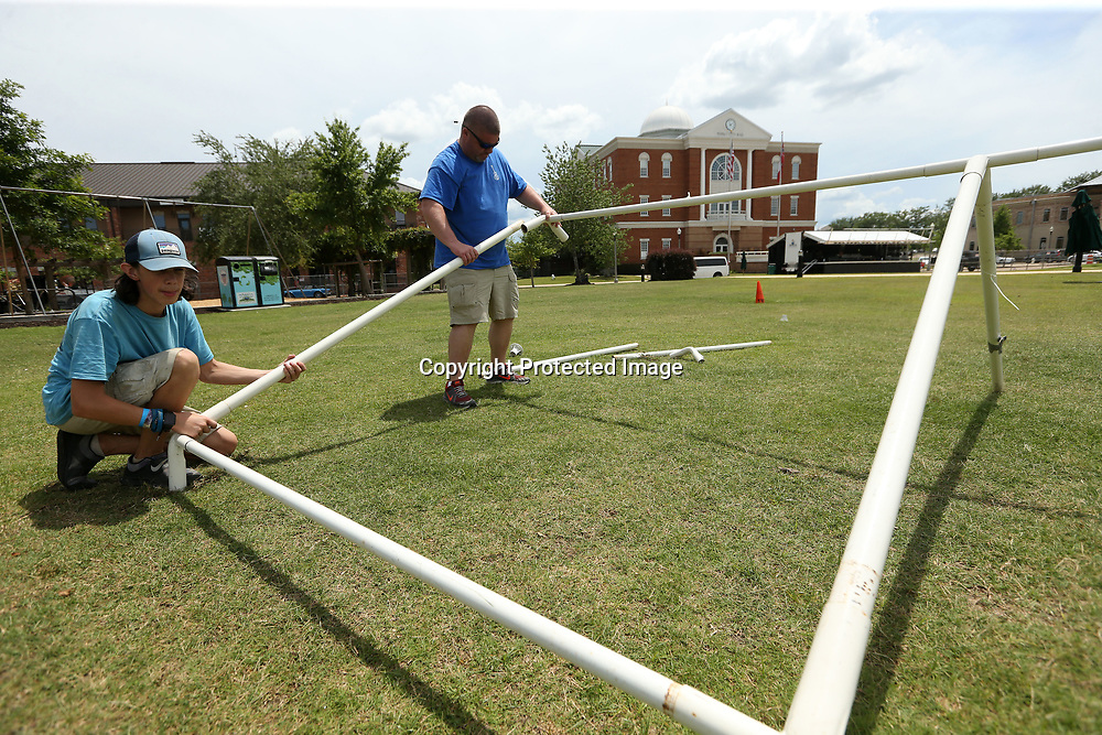 Hunter Spencer and Mark Young, members of the site team for the Tupelo Downtown Main Street Association, set up the poles for the merchandise tent at Fairpark for this weekend's Elvis Festival on Tuesday afternoon.