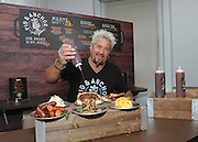 Food Network Star Guy Fieri serves up food from his new Pig & Anchor Bar-B-Que Smokehouse, exclusively on Carnival Cruise Line, at Carnival's Summertime Beer-B-Que, Wednesday, July 27, 2016, in New York.  (Diane Bondareff/ AP Images for Carnival Cruise Line)