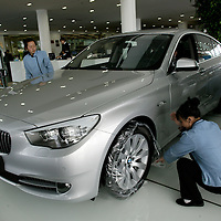 BEIJING, APRIL-22, 2010:   employees  take off plastic  from tyres at the BMW dealership .