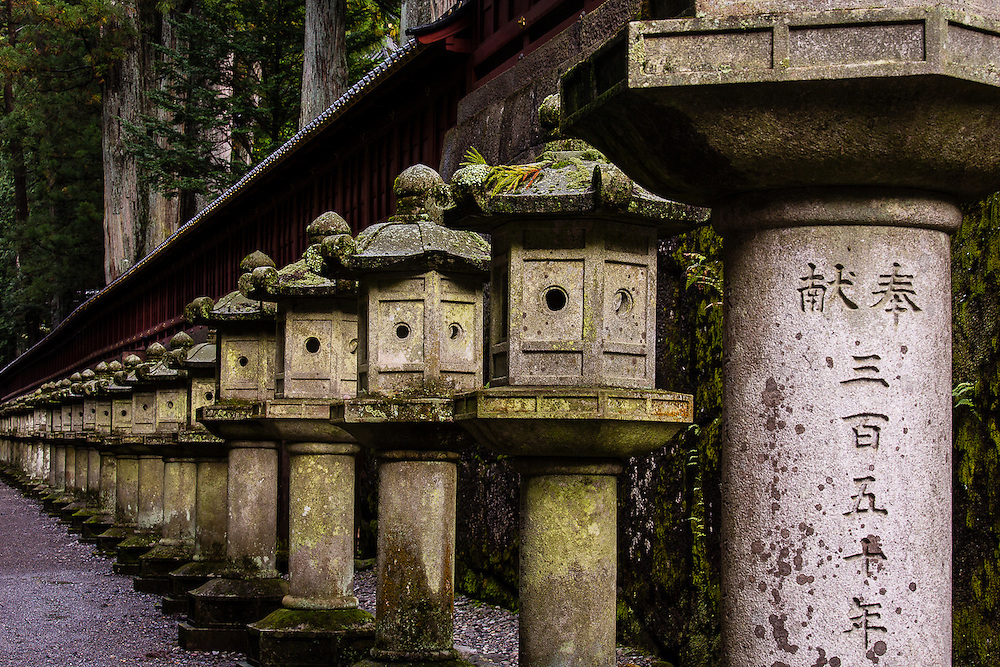 Near the stairs to the Tokugawa Mausoleum, a wall is lined up with stone lanterns, some of them bearing inscriptions in kanji.