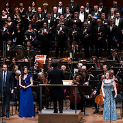 """November 21, 2013 - New York, NY :  Conductor Alan Gilbert, on podium at center, the New York Philharmonic, the New York Choral Artists, and the Brooklyn Youth Chorus, along with vocal soloists, tenor Dominic Armstrong (in tie standing at left), soprano Kate Royal (standing at center left in violet dress) and mezzo-soprano Sasha Cooke (standing in sequined dress at right) take a bow after performing Bejamin Britten's """"Spring Symphony, Op. 44 (1948-49)"""" with the New York Philharmonic at Avery Fisher Hall at Lincoln Center on Thursday night. Armstrong made his NY Phil debut as a last-minute substitution for tenor Paul Appleby, who withdrew due to illness. CREDIT: Karsten Moran for The New York Times **THIS IMAGE IS A CROP VARIATION**"""