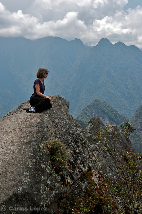 A woman is siting in the top rock of the wayna picchu looking to the landscape in cusco, peru.