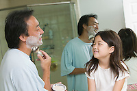 Daughter watching father apply shaving cream in bathroom