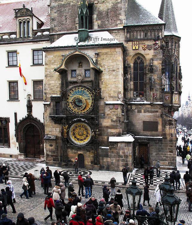 View of part of Old Town Square and City Hall with the restored astronomical clock below which a small crowd is gathering.  See http://en.wikipedia.org/wiki/Prague_Astronomical_Clock for a detailed history and technical survey of the clock, its mechanisms, and its sculptures.