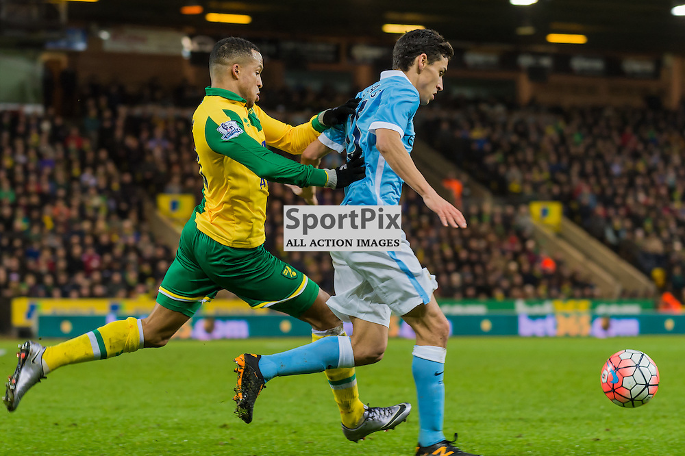 Manchester City midfielder Jesus Navas (15) gets ahead of Norwich City defender Sebastien Bassong (6)