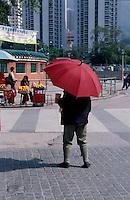 Woman with red umbrella in Kowloon, Hong Kong, China.