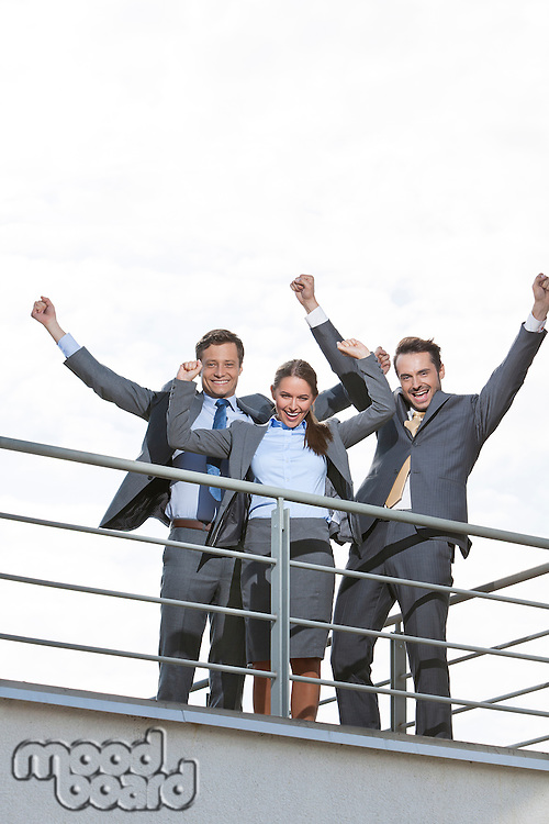 Low angle view of excited businesspeople with arms raised on terrace against sky