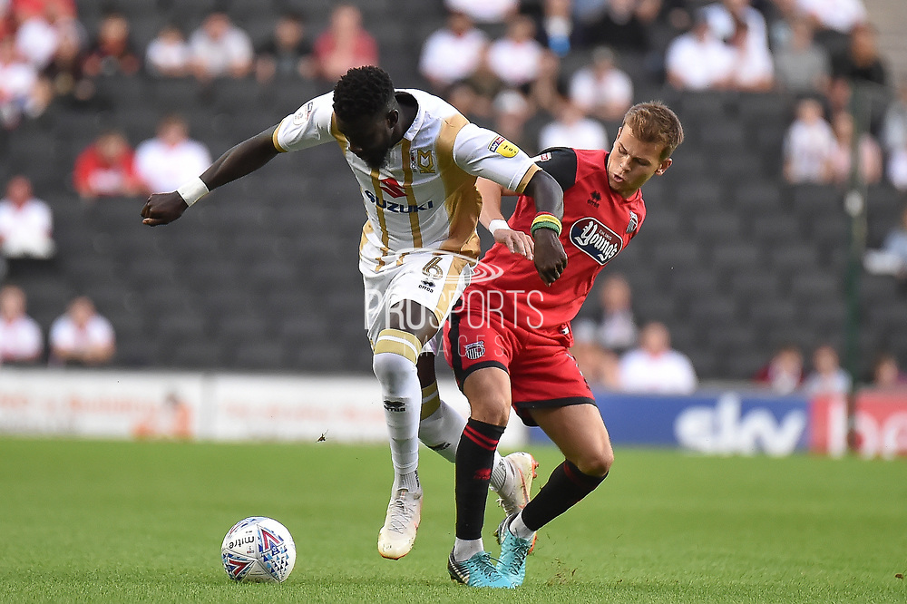 Milton Keynes Dons midfielder Oussseynou Cisse (6) battles for possession  with Grimsby Town defender Paul Dixon (3) during the EFL Sky Bet League 2 match between Milton Keynes Dons and Grimsby Town FC at stadium:mk, Milton Keynes, England on 21 August 2018.