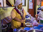 13 JULY 2013 - BANGKOK, THAILAND:  A Thai Muslim makes food for Iftar (the Muslim meal that breaks the day long fast) during Ramadan. Ramadan is the ninth month of the Islamic calendar, and the month in which Muslims believe the Quran was revealed. The month is spent by Muslims fasting during the daylight hours from dawn to sunset. Fasting during the month of Ramadan is one of the Five Pillars of Islam. Muslims believe that the Quran was sent down during this month, thus being prepared for gradual revelation by Jibraeel (Gabriel) to the prophet Muhammad.        PHOTO BY JACK KURTZ