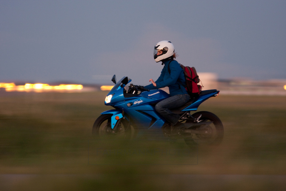 A woman dressed in all blue rides her Kowasaki Motorcycle at dusk