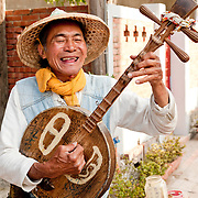 A colorful Taiwanese musician plays his yue chin and sings on old street in Yen Shui Village, Tainan County, Taiwan
