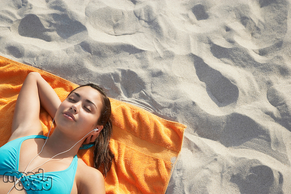 Teenage girl (16-17) using mp3 player lying on beach elevated view