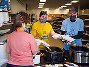 "26 APRIL 2020 - JEWELL, IOWA: MARCIE KNOLL, left back to camera, CARA ZANKER, center and KENN OUTZEN, members of the group trying to reopen a grocery store in Jewell, plate up roast pork dinners for grab and go meals. Jewell, a small community in central Iowa, became a food desert when the only grocery store in town closed in 2019. It served four communities within a 20 mile radius of Jewell. Some of the town's residents are trying to reopen the store, they are selling shares to form a co-op, and they hold regular fund raisers. Sunday, they served 550 ""grab and go"" pork roast dinners. They charged a free will donation for the dinners. Despite the state wide restriction on large gatherings because of the COVID-19 pandemic, the event drew hundreds of people, who stayed in their cars while volunteers wearing masks collected money and brought food out to them. Organizers say they've raised about $180,000 of their $225,000 goal and they hope to open the new grocery store before summer.           PHOTO BY JACK KURTZ"