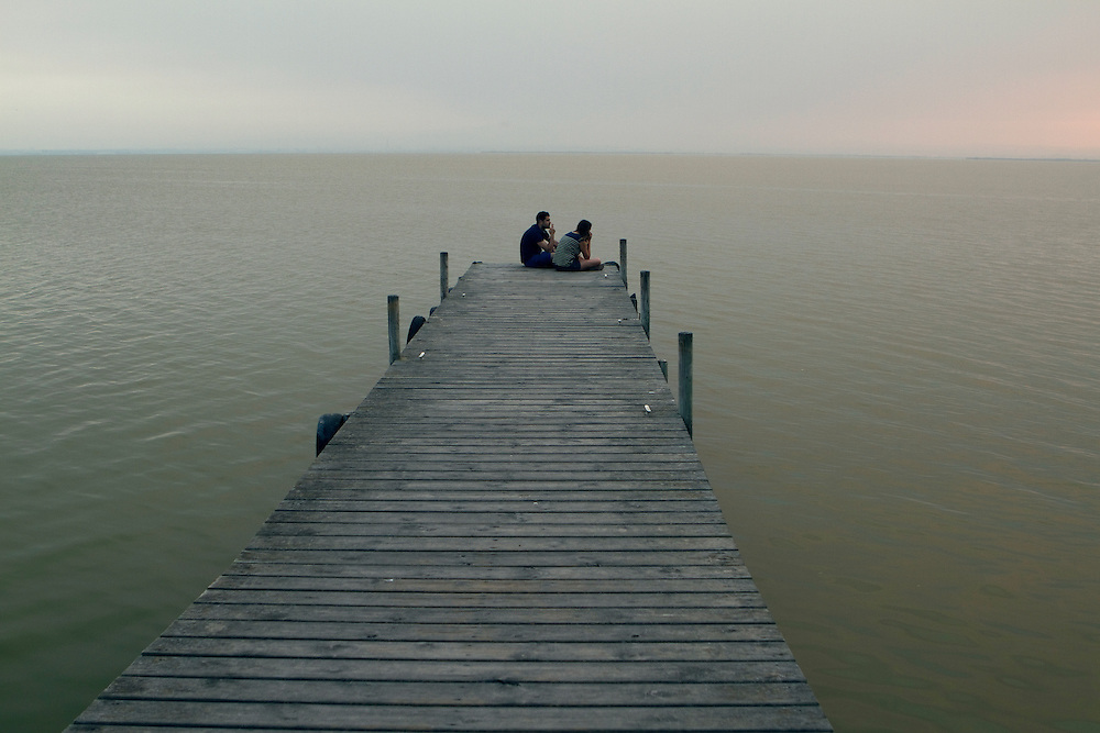Two young men enjoy a peaceful afternoon watching the landscape at La Albufera National Park, in Valencia, Spain.