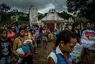 URDANETA, VENEZUELA - AUGUST 17, 2017: Children carried the coffin of three-month old, Kleiver Enrique Hernández for over two and a half hours, over hills and through shallow streams, during his funeral procession to the cemetery from the rural farming area where he lived with his family. Kleiver was born healthy, weighing 8 pounds 2 ounces - however his mother Kelly Hernández had difficulty nursing him. Her nipples would bleed heavily while feeding him, causing Kleiver to reject being nursed. Infant formula was inaccessible as an alternative because of widespread shortages, so Kelly had to improvise with what was available.  She prepared bottles for Kleiver with cornstarch and water, or occasionally with whole milk, when she could find it. Milk is also very difficult to find in Venezuela because of shortages. He did not get the nutrients he needed to grow, and was not gaining enough weight. He went into septic shock due to severe malnutrition and died after 20 days in the hospital. PHOTO: Meridith Kohut for The New York Times